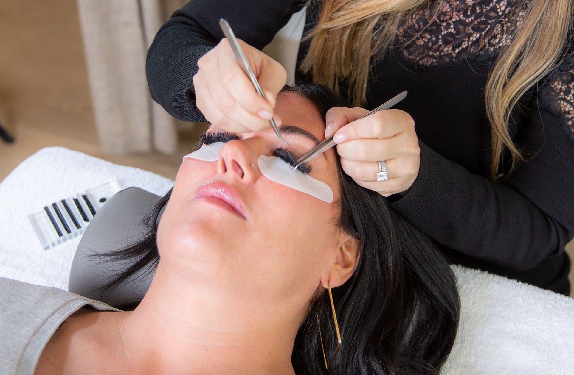woman receiving full set of eyelash extensions in studio