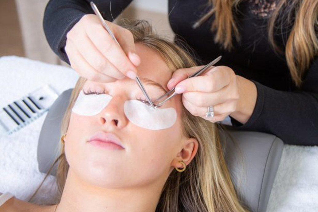 esthetician doing eyelash extensions on blonde woman