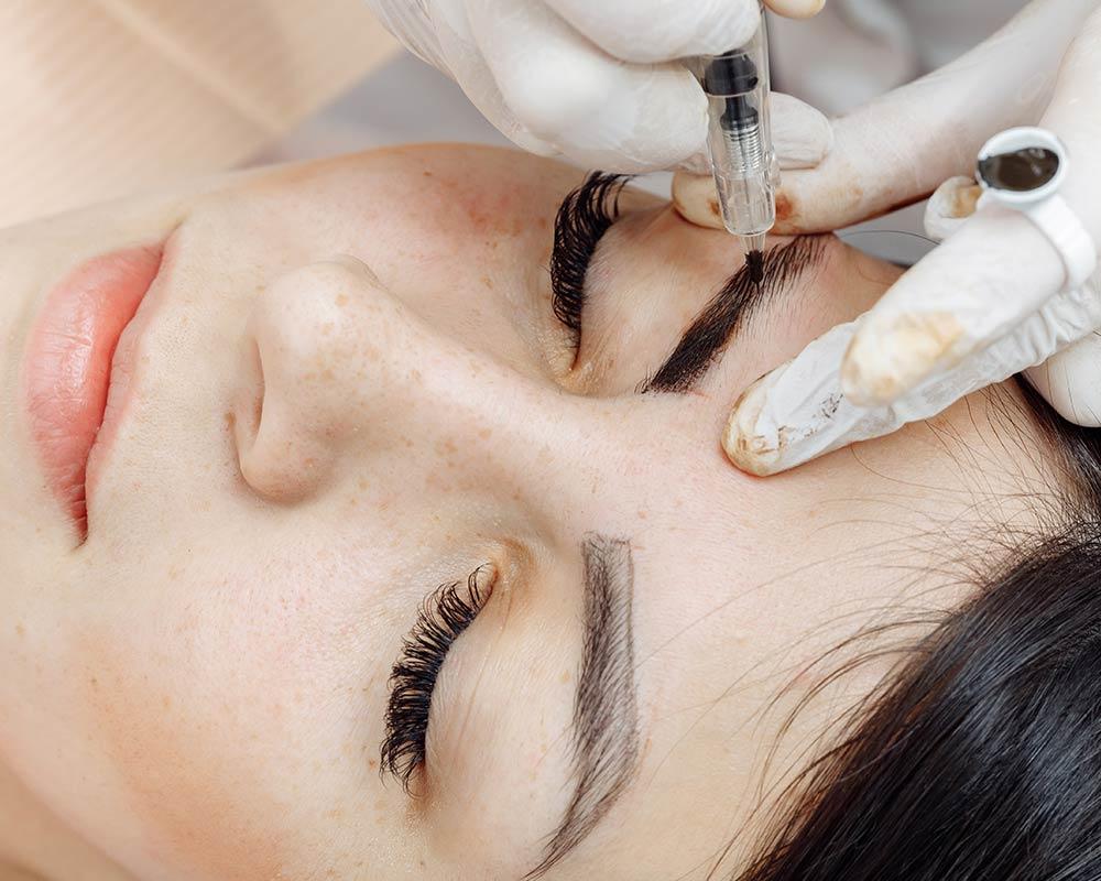woman receiving permanent makeup eyebrow service